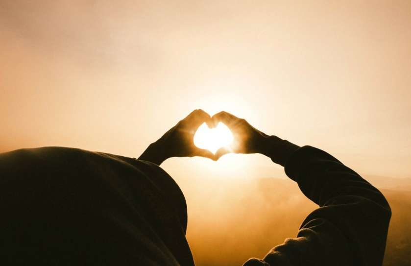 holding hands in the shape of a heart against the sunrise or sunset