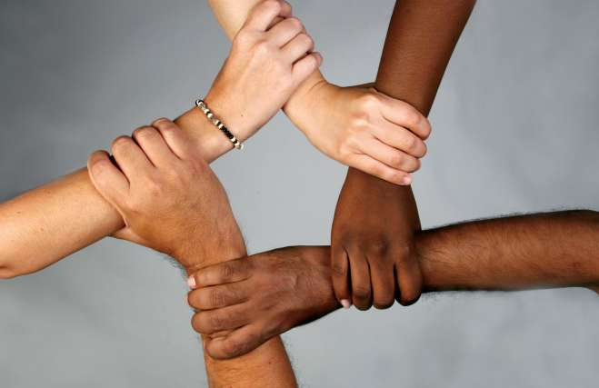people of different skin colors holding each others wrists in a symbol of unity