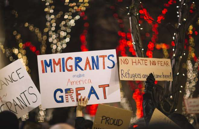 """photo of a rally for immigrants with people holding signs, the one in the center says """"Immigrants Make America Great"""""""
