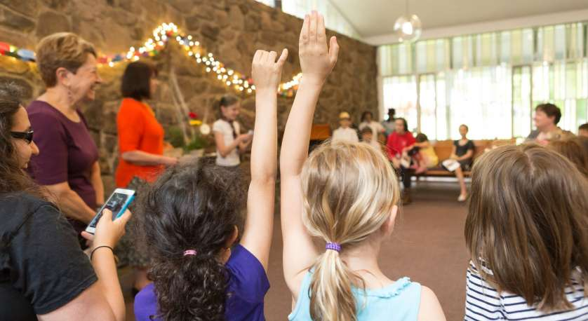 photo of children raising hands during a Chapel service for all ages