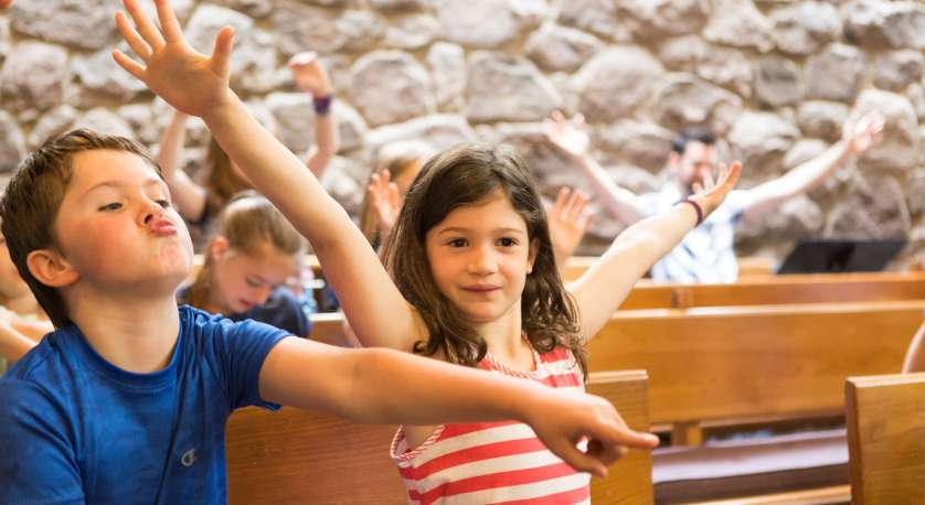 younger children in Cedar Lane's Chapel for all ages short worship service, children are making funny faces and holding hands up