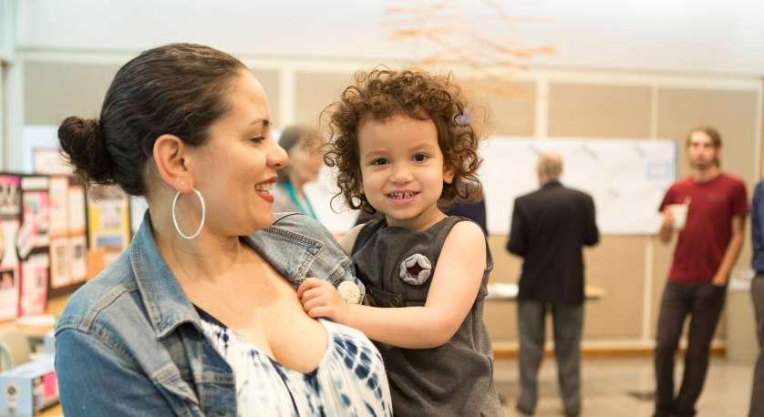 mother holding toddler at Cedar Lane inside the Lounge