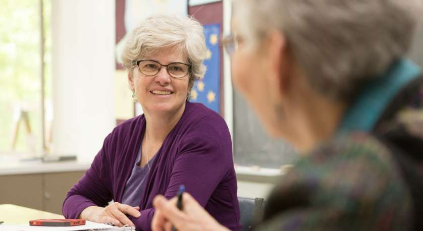 photo of cedar lane member smiling at another member across a table during a meeting while seated
