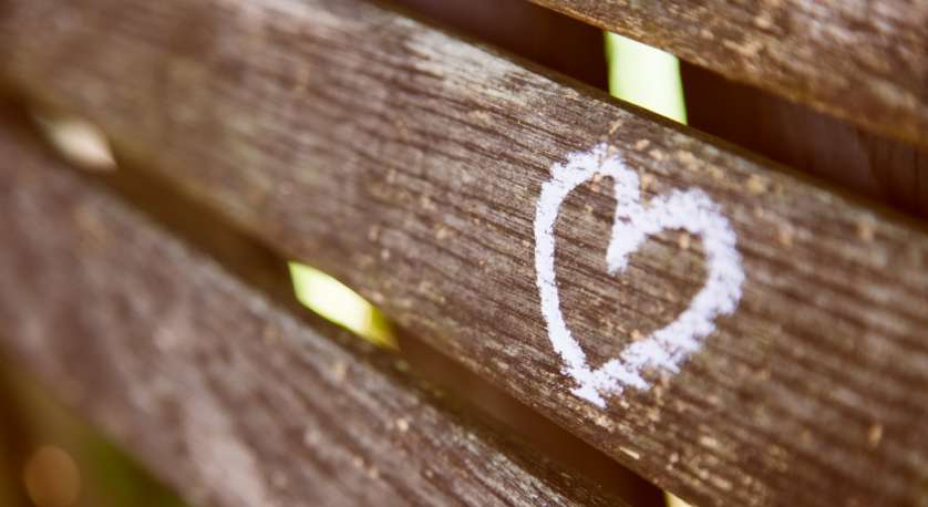 photo of a heart drawn in chalk on a wooden fence outside