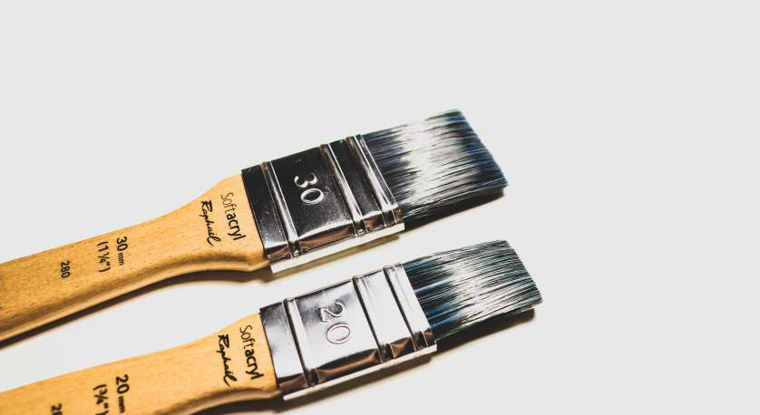 paint brushes with white paint on the tips against a white background