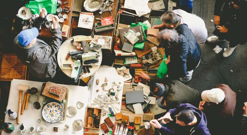 photo looking down on people going through flea market items on tables