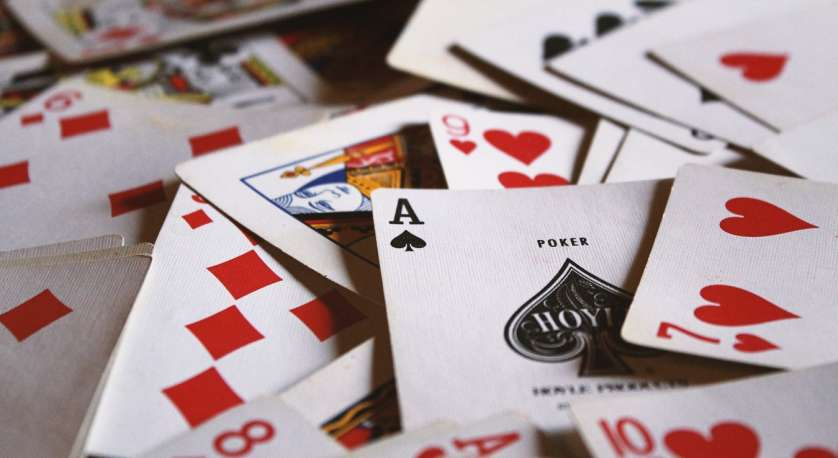 bunch of playing cards spread over a table