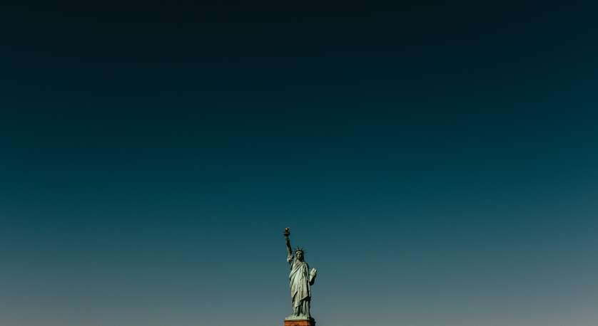 distant shot of the statue of liberty against a very dark blue sky