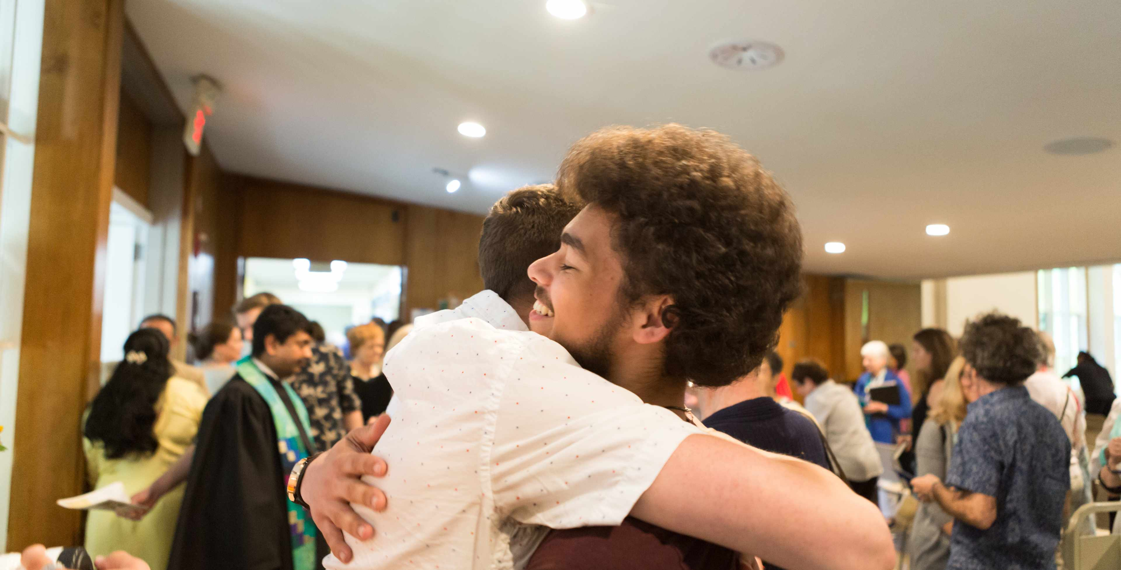 two members hugging after Sunday worship
