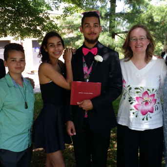 a church member and her three children celebrating the graduation of one of her sons