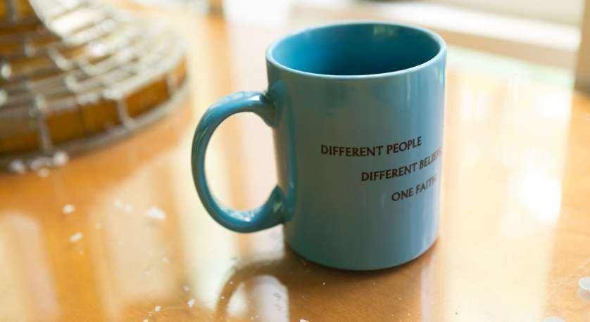 """coffee mug on a table that says """"different people, different beliefs, one faith"""""""