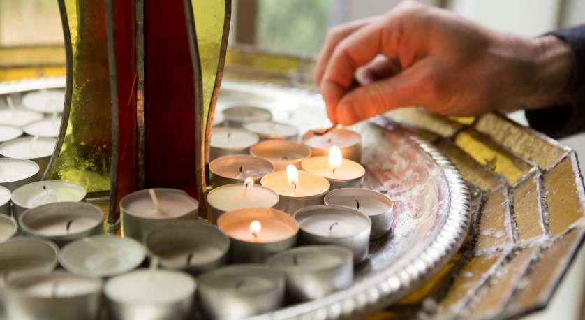 hand lighting a candle by the large Chalice in the Sanctuary at Cedar Lane