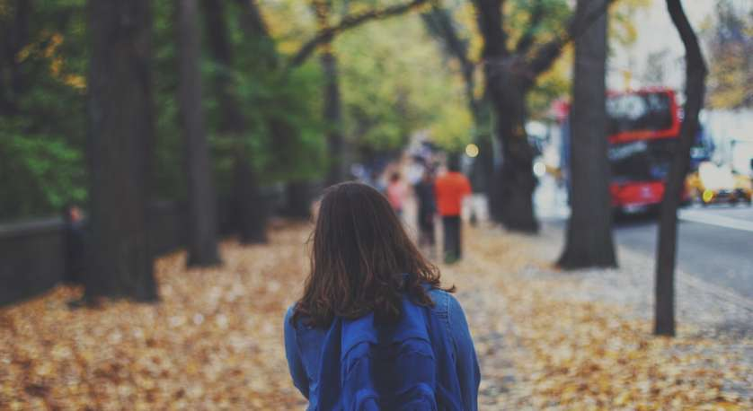 photo of girl with backpack walking down a sidewalk with kids up in front of her and fall leaves all around
