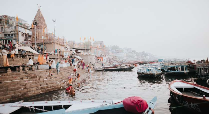stock photo of boats on water on the side of a city in India with plenty of people wandering around