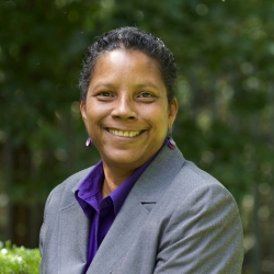 head shot of Archene Turner, Community Minister at Cedar Lane in the courtyard with greenery behind her