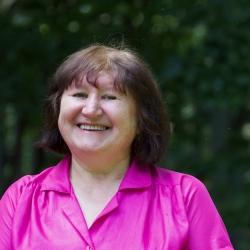 head shot of Lucy Dubinsky in bright pink shirt in Cedar Lane courtyard